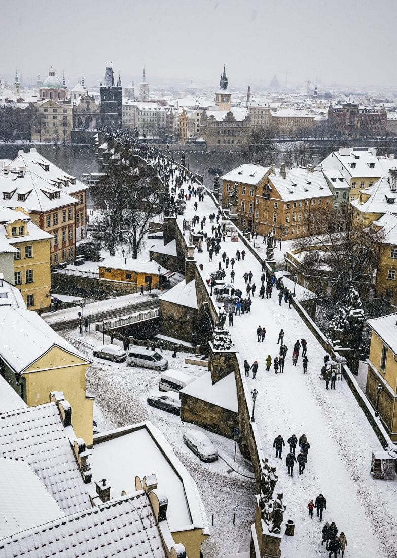 the charles bridge during snowfall in Prague