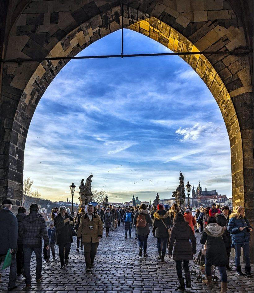 People walking across the Charles bridge in Prague