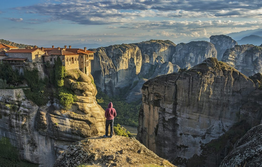 man standing on rocky cliff overlooking a monastery in Meteora Greece