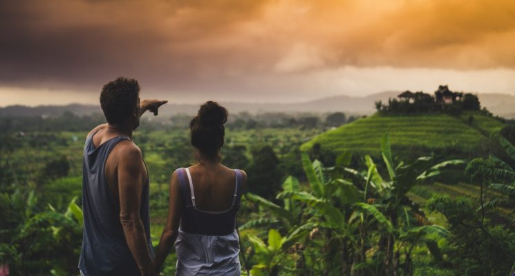 man and woman looking over a lush green landscape in Bali on one of the best Bali tours