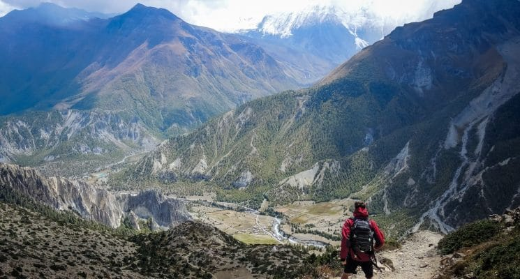 Man looks down at Manang on the Annapurna trail in Nepal