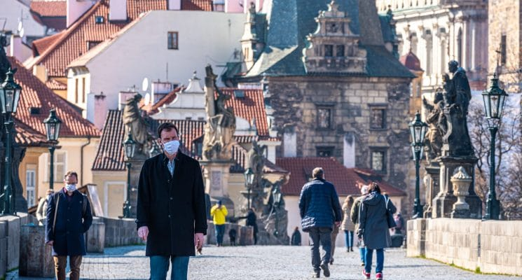 man wearing mask charles bridge prague pandemic
