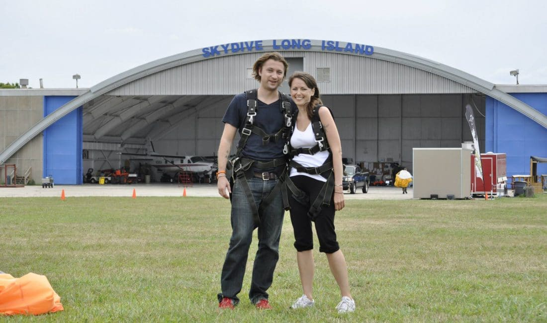 two people standing outside of a skydiving center