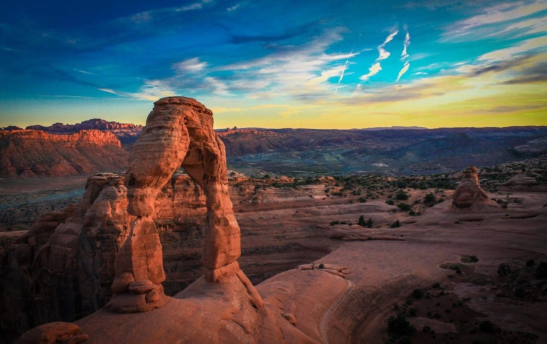 a natural sandstone arch formation in Arches National Park Utah with a sunset in the background