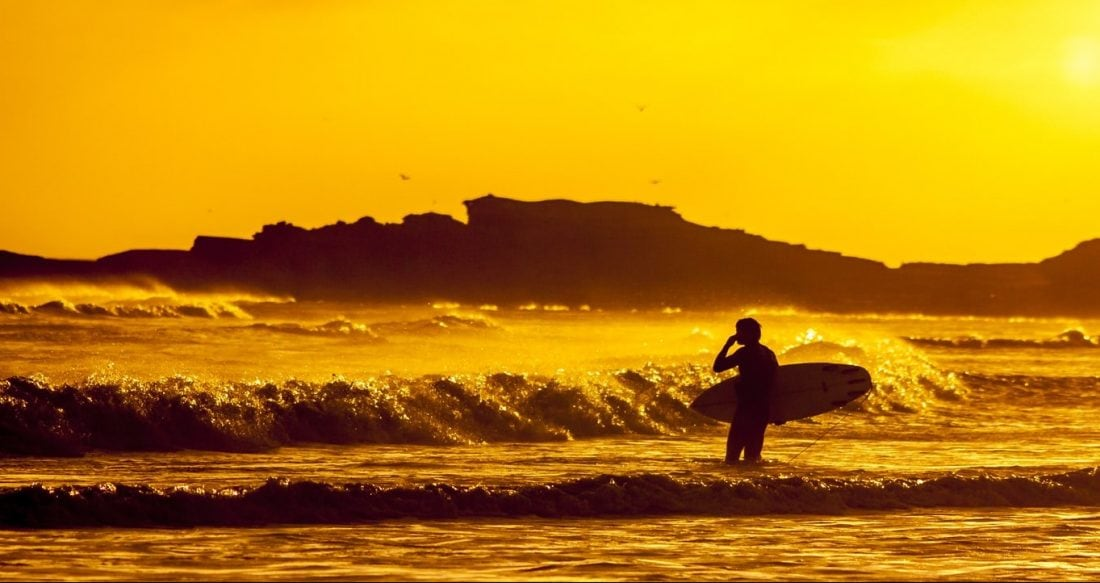a surfer jusging the waves during sunset in Ensenada