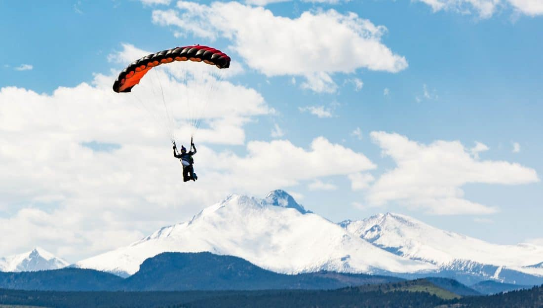 a skydiver floats down with chute deployed with the Rockies in the background in Longmont. Photo courtesy the Mile Hi Skydiving Center