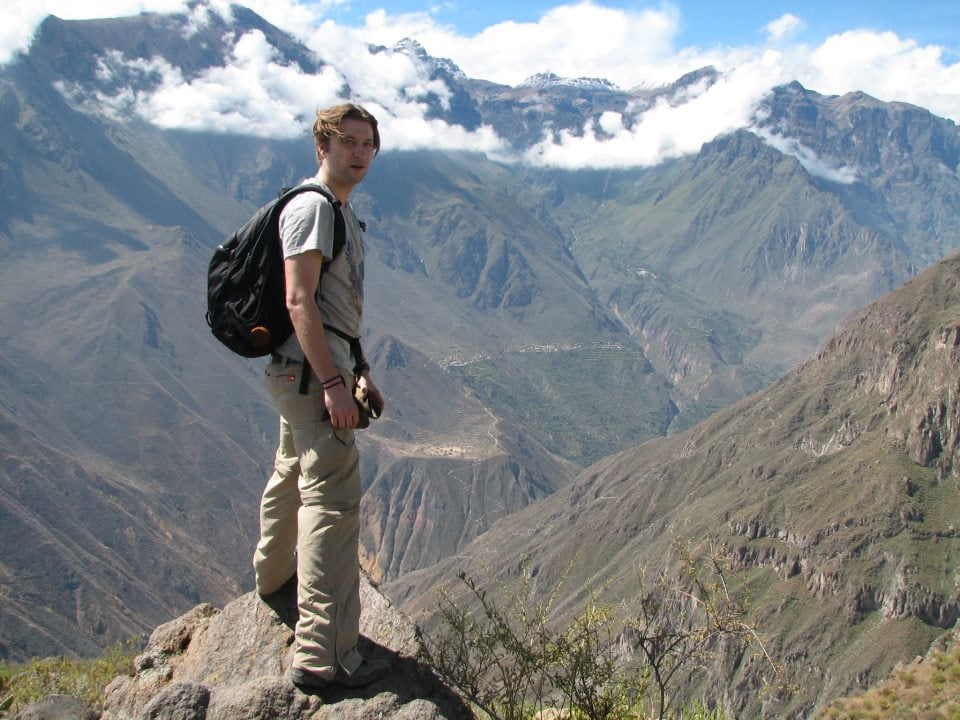 Man standing on a rock overlooking a beautiful valley in Peru