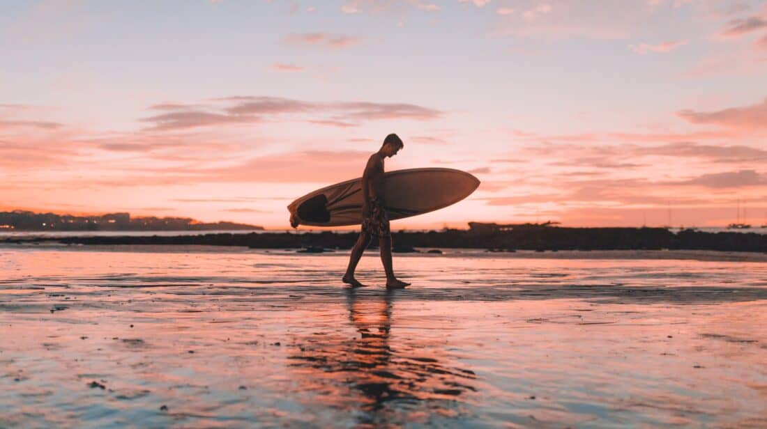 man carrying surfboard on beach in Costa Rica pink sky