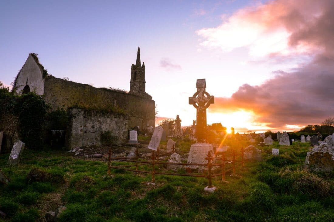 sunset over a cemetery and church in cork ireland